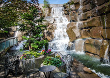 Waterfalls in a garden park on a summer day. The waterfalls of a secluded, enchanting garden in an urban setting provides chairs and small tables in a peaceful Stock Photography