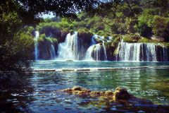 Waterfalls in Krka National Park in Croatia. Waterfalls framed by foliage in Krka National Park in Croatia – Made with a retro style purple film technique stock photography