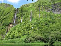 Waterfalls at Lagoa dos Patos on Flores island, The Azores. Narrow waterfalls down a vegetated cliff to Lagoa dos Patos on the island of Flores, the Azores royalty free stock images