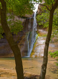 Waterfalls on Lower Calf Creek framed by trees. Lower Calf Creek Falls in Grand Staircase - Escalante National Monument in southern Utah can only be reached via Royalty Free Stock Photos