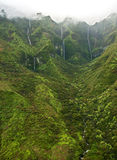 Waterfalls and mist - Kauai. A helicopter view of waterfalls draining from the lush south side of Mount Waialeale (Wai'ale'ale), Kauai. The summit is often Royalty Free Stock Photo