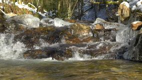 Waterfalls on mountain river slow motion view, clearness and freshness of nature. Winter sunny day. Snow and beautiful ice stock video footage