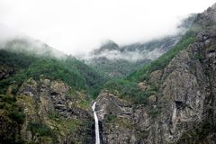 Waterfalls Between Mountain Rocks in Foggy Place Stock Photography