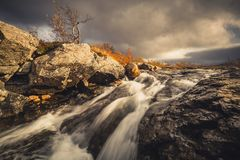 Waterfalls on mountain stream. Autumn in Sylan mountains in Norw. Ay. Stugudalen area. Dark clouds and colorful leaves stock image