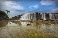 Waterfalls Near Hills Under Blue Sky and White Clouds Stock Image
