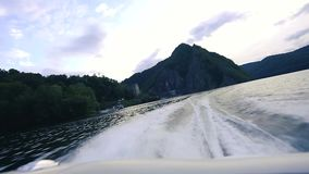 Waterfalls and rivers in forest touristic trailTail of a boat cruising on Vidraru Lake. Tail of a boat cruising on Vidraru Lake at sunset. Fagaras Mountains on stock footage