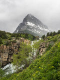 Waterfalls and snow capped mountain. Water tumbles through a rocky canyon with a snow-capped mountain on a cloudy day at Many Glacier in Glacier National Park stock photo