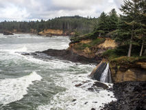 Waterfalls into surf on rugged coast. A waterfalls lands in the surf at the rugged coast of Boiler Bay on the Oregon coast Royalty Free Stock Photo