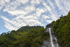 Waterfalls Surrounded by Green Leaved Trees Under Blue and White Cloudy Sky during Daytime Royalty Free Stock Photos