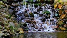 Waterfalls in a tropical garden. Beautiful waterfalls surrounded by rocks in a tropical garden in hong kong stock video footage