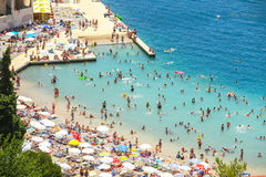 Waterfont and beach in Neum. NEUM, BOSNIA AND HERZEGOVINA - JULY 16, 2017 : A view of the town waterfront and people swimming and sunbathing on the beach in Neum Stock Photos