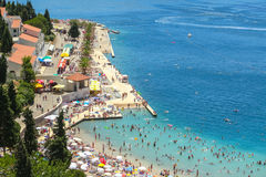 Waterfont and beach in Neum. NEUM, BOSNIA AND HERZEGOVINA - JULY 16, 2017 : A view of the town waterfront and people swimming and sunbathing on the beach in Neum Royalty Free Stock Photos