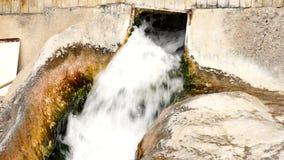 Waterfontein die tussen rotsen uitstorten stock videobeelden