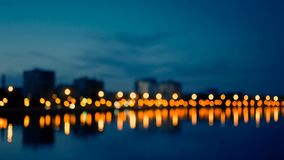 Waterfront area of city in night time, defocused shot of street lights blurred. Deep blue vintage tones stock footage