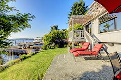 Waterfront back yard, Furnished back patio with red chairs, and Royalty Free Stock Photography