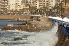 Waterfront, Beirut. People on the rocks with the waves lapping the sea wall, waterfront, Beirut Royalty Free Stock Images