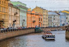 Waterfront buildings on the banks of river Neva and tourist boats on the water in Saint Petersburg stock images
