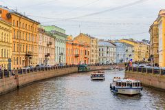 Waterfront buildings on the banks of river Neva and tourist boats on the water in Saint Petersburg royalty free stock image