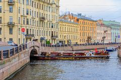 Waterfront buildings on the banks of river Neva and tourist boats on the water in Saint Petersburg stock image