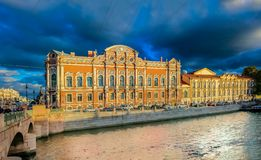 Waterfront buildings on the banks of river Neva and tourist boats on the water in Saint Petersburg royalty free stock photo