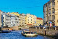 Waterfront buildings on the banks of river Neva and tourist boats on the water in Saint Petersburg stock photography