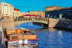 Waterfront buildings on the banks of river Neva and tourist boats on the water in Saint Petersburg royalty free stock photos