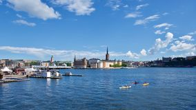 Waterfront buildings in Stockholm , Sweden. Panoramic view of scenic waterfront buildings in Stockholm , Sweden with three canoeists in the foreground Stock Photo