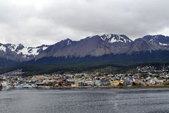 Waterfront in Ushuaia Harbor, Argentina. Waterfront buildings under snow capped mountains looking into the town from Ushuaia Harbor, approaching from the Beagle Stock Image