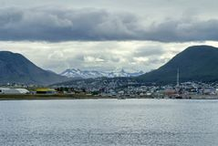 Waterfront in Ushuaia Harbor, Argentina. Waterfront buildings under snow capped mountains looking into the town from Ushuaia Harbor, approaching from the Beagle Royalty Free Stock Images