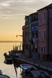 Waterfront canal on the island of Burano, houses and boats Royalty Free Stock Photo