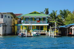Free Waterfront Caribbean Home With Boats At Dock Stock Photography - 76038362