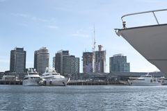 Waterfront City and boats. View at buildings of Waterfront City in Docklands with boat deck, constructed buildings and white luxury boats in Victoria Harbor in Stock Photography