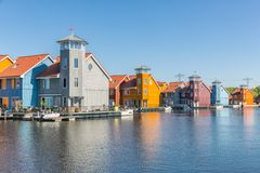 Waterfront with colorful wooden houses in Dutch Reitdiep harbor, Groningen stock images