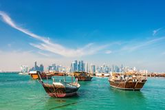 Waterfront in Doha. Qatar with traditional wooden small ships known as dhow and city skyline Royalty Free Stock Image