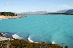 Idyllic waterfront with dramatic milky bluish green water, distant trees and mountains. Landscape on deep aqua color Lake Pukaki, Canterbury, South Island, New stock photography