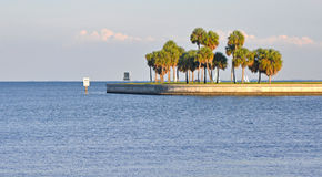 Waterfront entrance to a bay. Waterfront entrance to the St. Petersburg Bay, Florida, with some palm trees alongside a beach walkway, on a sunny day Royalty Free Stock Photo