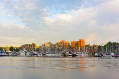 Waterfront False Creek suburb during sunrise, Vancouver, British Columbia, Canada. Residential buildings, moored yachts, and floating houses along the sea shore Stock Photography