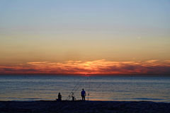 Couple fishing at beach by dusk Royalty Free Stock Images