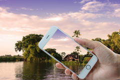 Waterfront home. Hand hloding smart phone at Waterfront home Royalty Free Stock Image