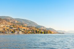 Waterfront homes and mountains on lake with blue sky and warm light from evening sunshine in autumn. Shoreline of Skaha Lake in Penticton, British Columbia stock image