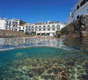 Waterfront hotel Cadaques fish underwater Spain. Waterfront hotel with beach in the village of Cadaques and some fish underwater, split view above and below Stock Photos