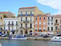 Waterfront hotel and small boat. Small boat moored at wharf and waterfront hotel in the city of Sete in France royalty free stock images