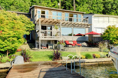 Waterfront house with large windows, furnished back patio and gr Royalty Free Stock Images