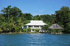 Waterfront house with thatched hut over the sea Royalty Free Stock Photo
