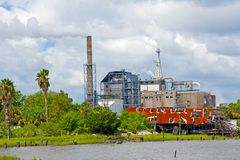 Waterfront industrial complex. Smokestacks and machinery from paper mill on rustic waterfront site Stock Images