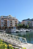 Waterfront Living. Catamarans moored in the tranquil harbor with apartment blocks in the background. Wooden gangway in the forefront royalty free stock photos