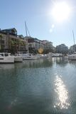 Waterfront Living. Sun sparkles on the calm harbor water with moored boats, catamarans and small yachts. Apartment blocks in the background royalty free stock photography