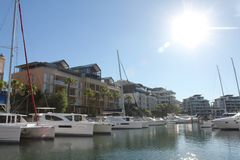 Waterfront Living. Yachts in the foreground with apartment blocks all around the harbour edge. Lifestyle stock photo