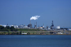 Waterfront Oil Refinery. Waterfront view of an oil refinery with storage tanks, smokestacks, and billowing smoke stock images