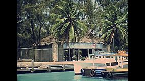 Bahamas Paradise Beach. Waterfront of Paradise Beach of Paradise Island through coastline and ports with fishing boats and hotels in 70`s with old buildings. The stock video footage
